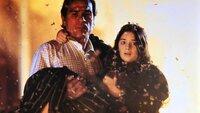 Mit seiner Tochter Kelly (Gaby Hoffmann) auf dem Arm flüchtet Mike Roark (Tommy Lee Jones) vor dem riesigen Lavastrom.