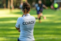 Rückansicht einer Sporttrainerin, die ihr Team auf einem Fußballplatz im Freien beobachtet