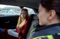 Amely (Charlotte Lorenzen) wird von einer Polizistin überwacht.