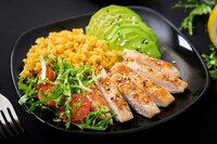 Healthy dish with chicken, tomatoes, avocado, lettuce and lentil on dark background