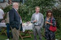 Bill Bradwell (James Cosmo, l.) ärgert sich darüber, dass sich sein Sohn Mark (Steven Robertson, M.) und dessen Frau Stella (Sunetra Sarker, r.) während einer Gartenparty über Geschäftliches unterhalten möchten.
