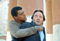Der afrikanische Straßenhändler Nando (Ernest Allan Hausmann) bedroht Brunetti (Uwe Kockisch, re.) und zwingt ihn zur Herausgabe der Diamanten, die der Commissario in seiner Unterkunft gefunden hat.