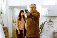 Daniela (Alice Gruia, l.) sucht Schutz hinter Klaus (Hartmut Volle, r.), der mit gezogener Waffe, den Entführern entgegentritt.