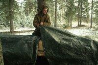 Gerrid checking snow covered tarp protecting birch bark canoe.