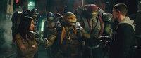 Die Reporterin April O'Neil (Megan Fox, l.) macht den Vollzugsbeamten Casey Jones (Stephen Amell, r.), der für den Gefangenentransport verantwortlich war, bei dem Shredder wie vom Erdboden verschwand, mit den Ninja Turtles Donatello (2.v.l.), Leonardo (3.v.l.), Michelangelo (3.v.r.) und Raphael (2.v.r.) bekannt ...
